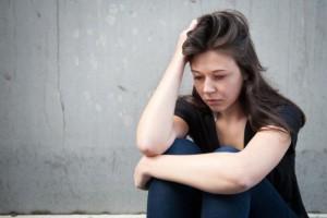 teenage-girl-sitting-and-looking-sad